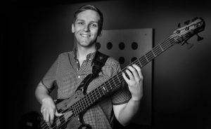 black and white image of Ben Hearn playing a Roscoe bass guitar.
